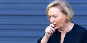 An older woman is coughing