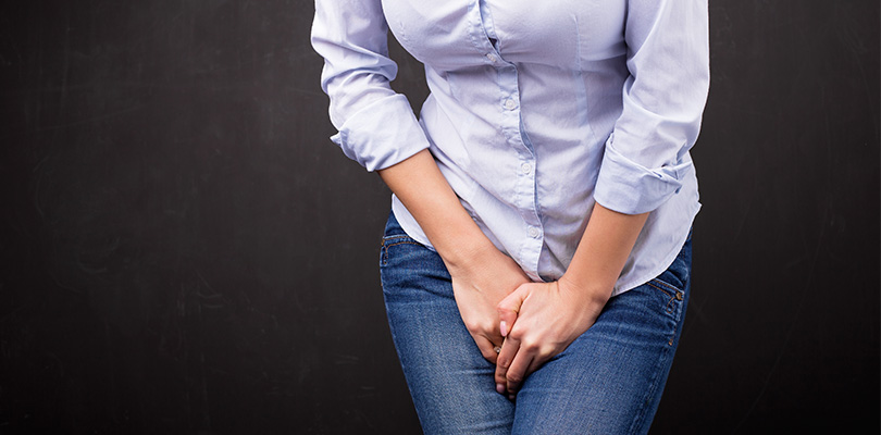 Woman with hands in front of pelvis