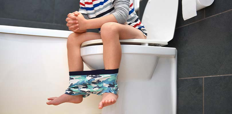 A child sitting on a toilet.