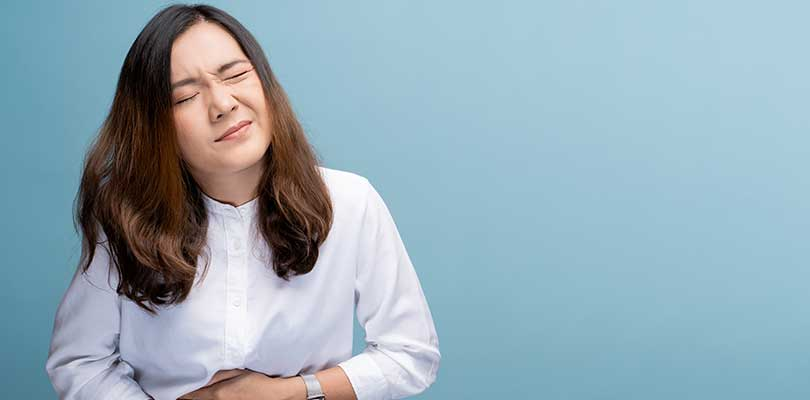 A woman holding her hand against her stomach and making a face as if in pain.